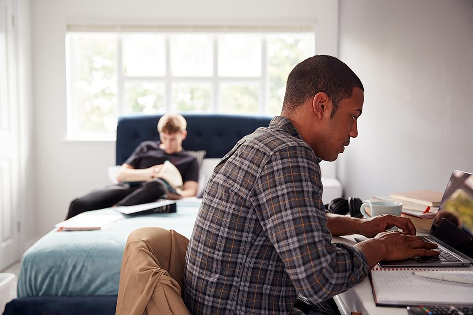 Two male students in shared house bedroom studying together.