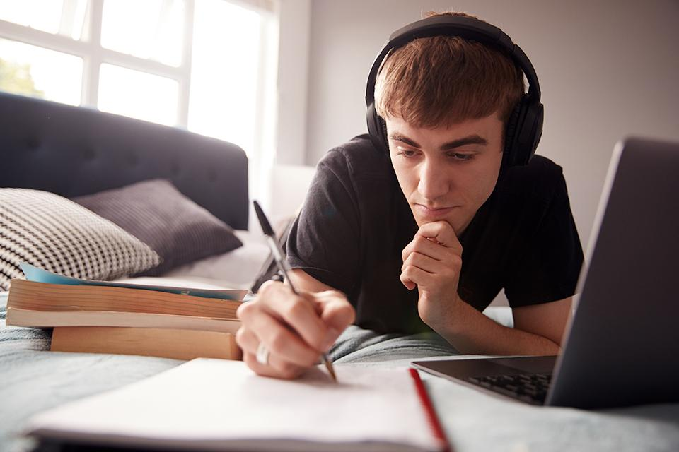 Student wearing headphones laying on bed.