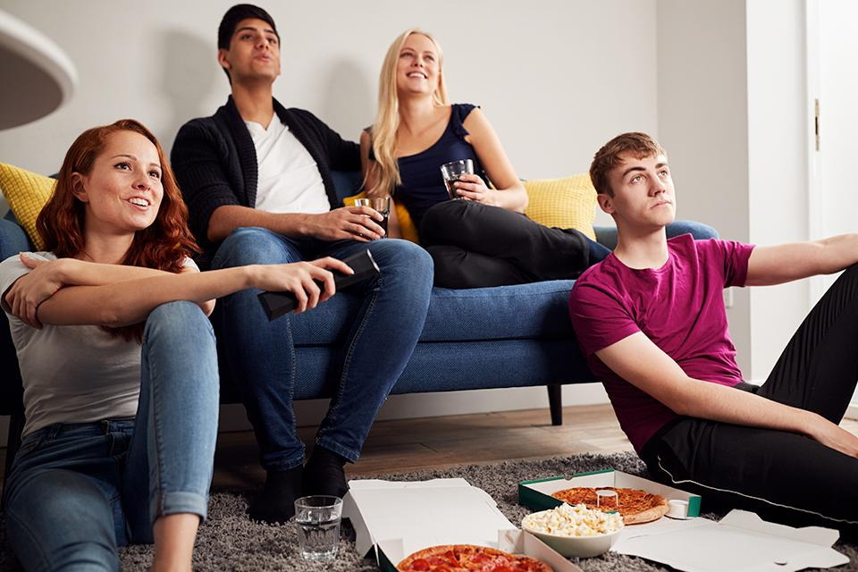 Group of students watching TV and eating pizza.