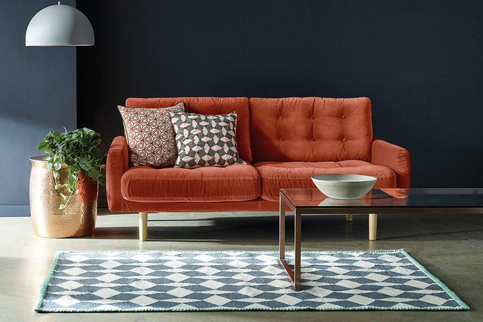 Velvet orange sofa with 2 cushions next to rug and glass coffee table.