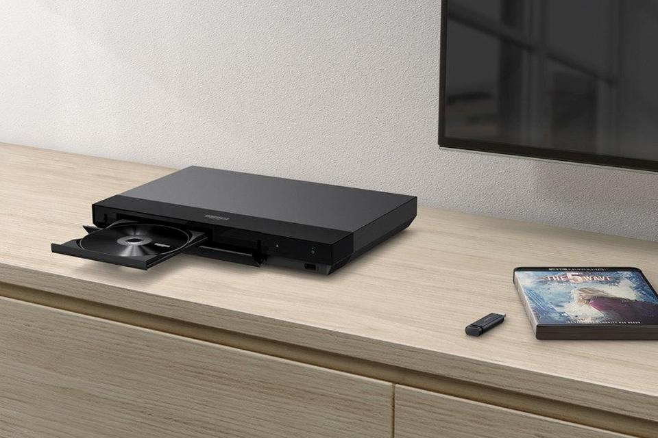 A 4K Blu-ray player with an open disc drive.
