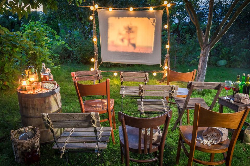 Summer cinema with retro projector in the garden.