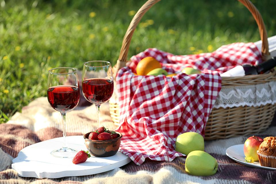 A picnic basket on a blanket with two glasses of red wine.