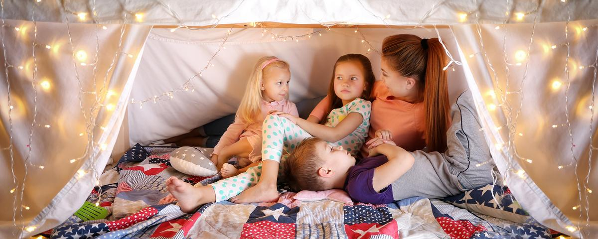 A mum and three children under a blanket fort with fairy lights surrounding.