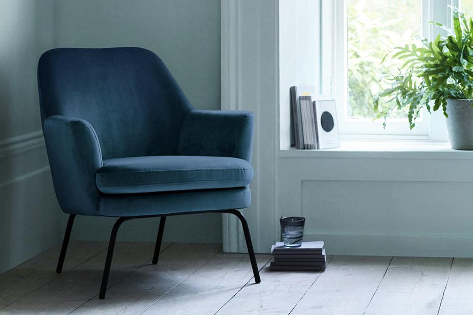 Velvet blue armchair positioned in the corner of a room.