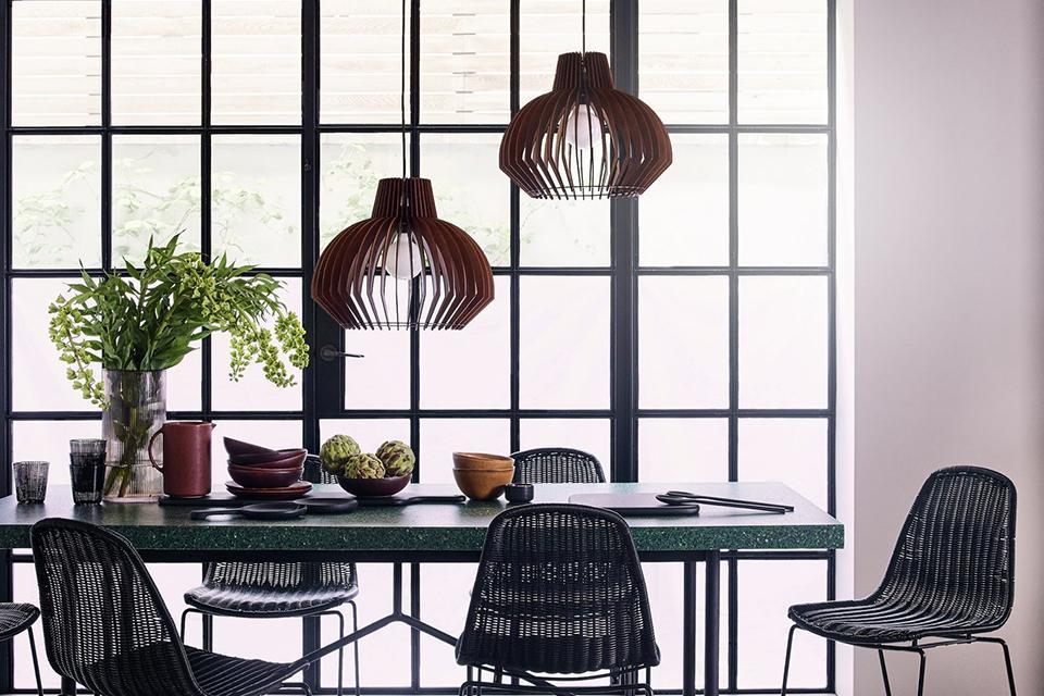 Set of 2 pendant shades over a rectangular dining set.