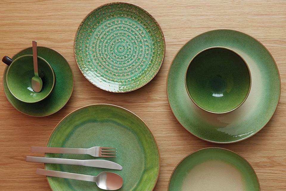Set of green stoneware crockery on top of a wooden table.