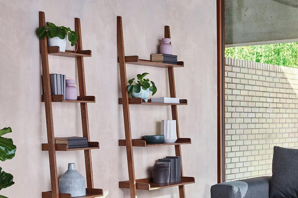 Image of 2 ladder shelving units leaning against an off-white wall.