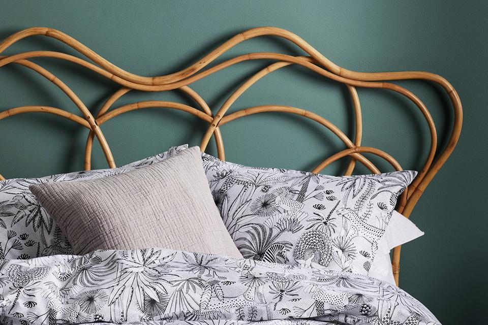 Patterned duvet on bed with wooden headboard.
