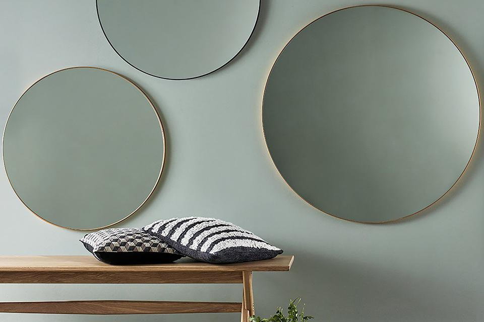 Image of 3 round mirrors on grey wall.
