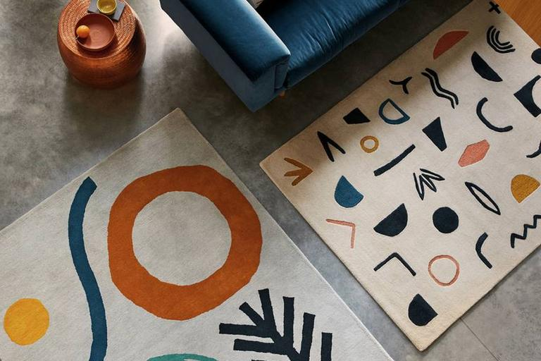 Image of 2 rugs with abstract design next to blue sofa.