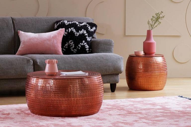 Image of a grey sofa with a round, rose gold metal coffee table.