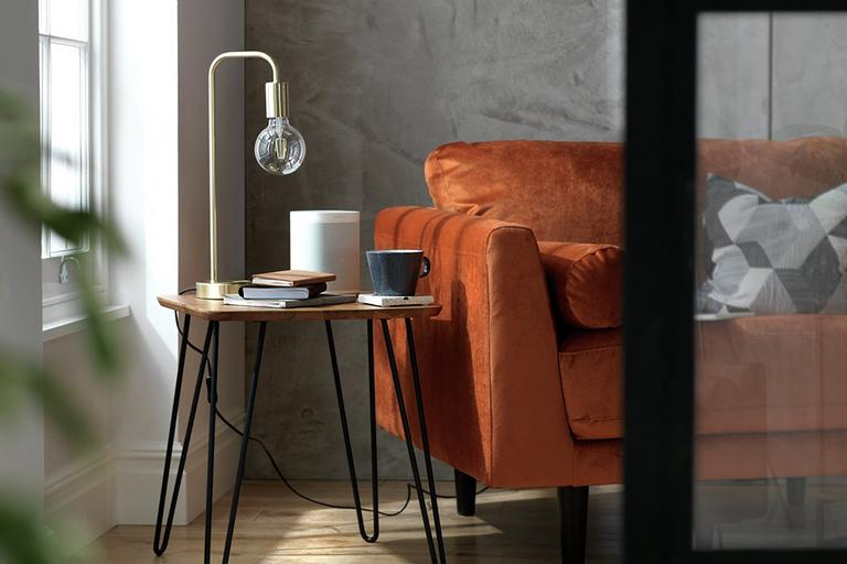 Image of an industrial-style side table with a wooden top and black, metal hairpin legs.