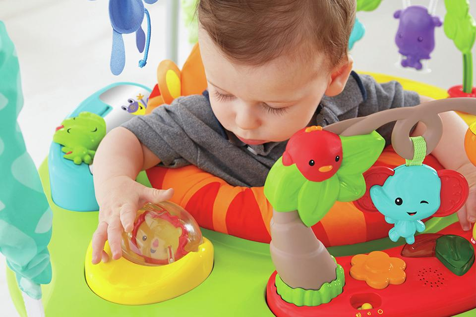 A baby plays with toys in a bouncer.