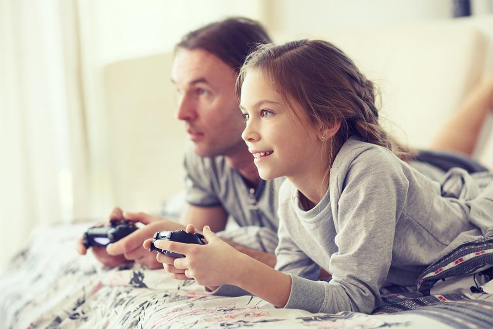 Child playing video game with father.