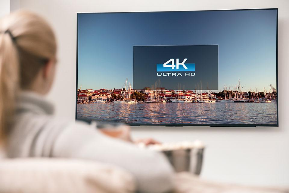 A woman watches a 4K TV.