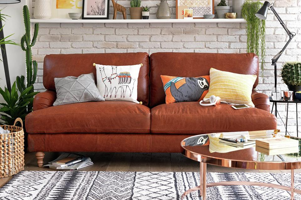 Sofa with cushions, coffee table and rug.