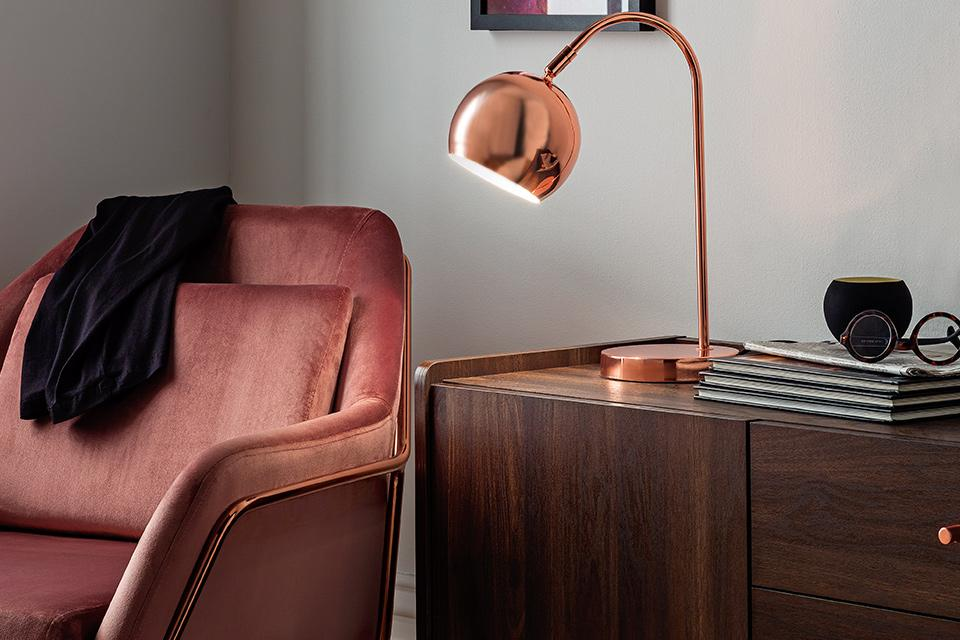 An elegant table lamp positioned on a sideboard next to an armchair.