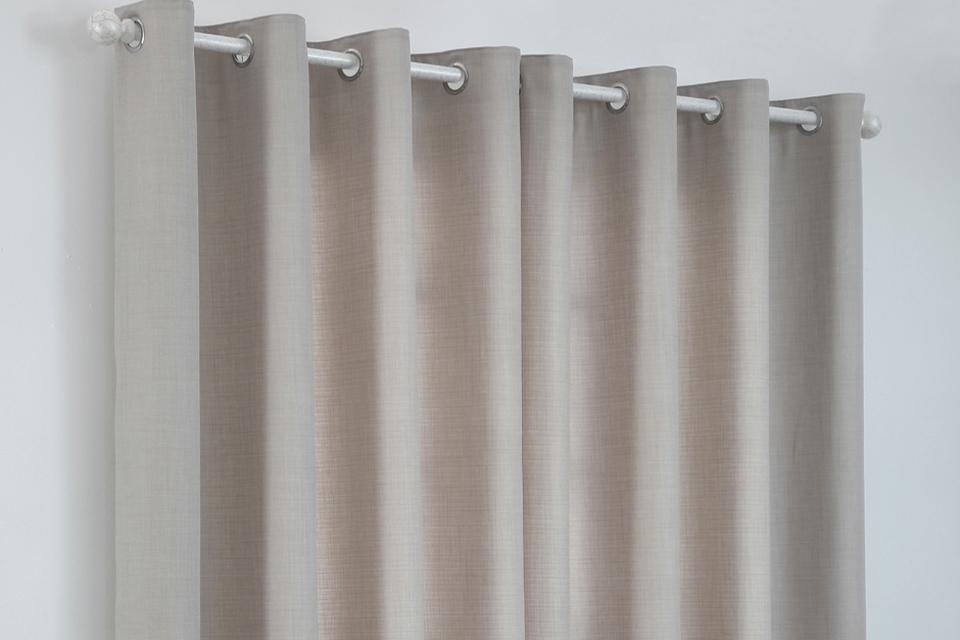 Argos Home fully line natural eyelet curtains, made from 100% recycled materials.
