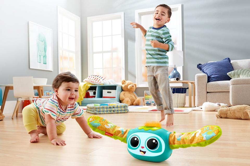 Two young boys playing in living room with Rollin' Rovee toy.