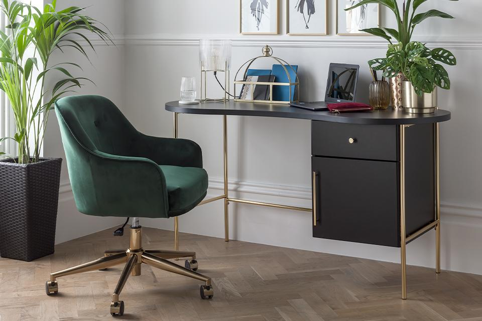 Image of a stylish home office. The focus of the shot is a black desk with gold metal legs, sitting next to a plush green velvet office chair.