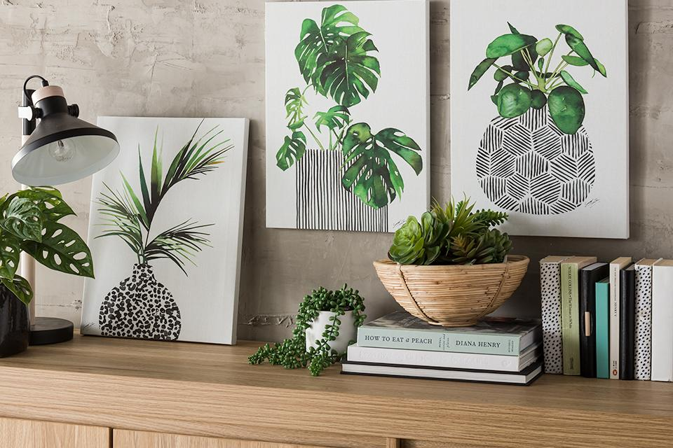 Image of bold artwork of illustrated green plants leaning against a wall.