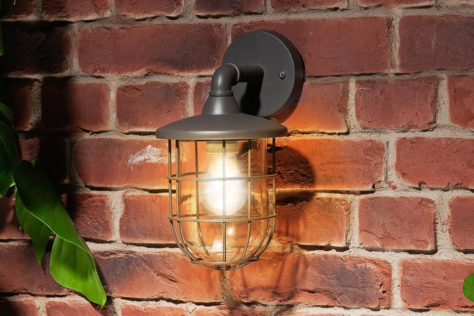 Image of a lantern-style outdoor wall lamp fixed to a brick wall. It's dusk outside and the lamp is on.