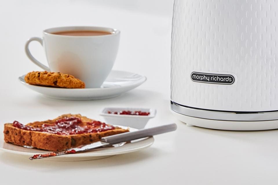 A Morphy Richards kettle beside a plate of toast and a hot drink.
