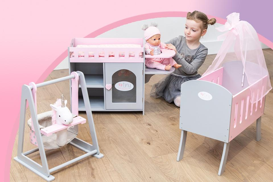 Image shows a girl playing with a Tiny Treasures doll, with accessories including a crib, baby changing station and swing.