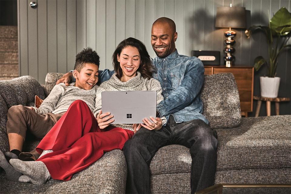 A family sitting on a sofa, using a laptop.