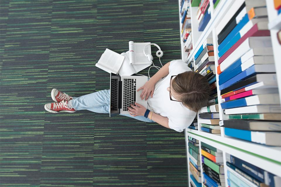 Birds-eye image of student sat up against a bookshelf on the floor of a library with a laptop on their lap.