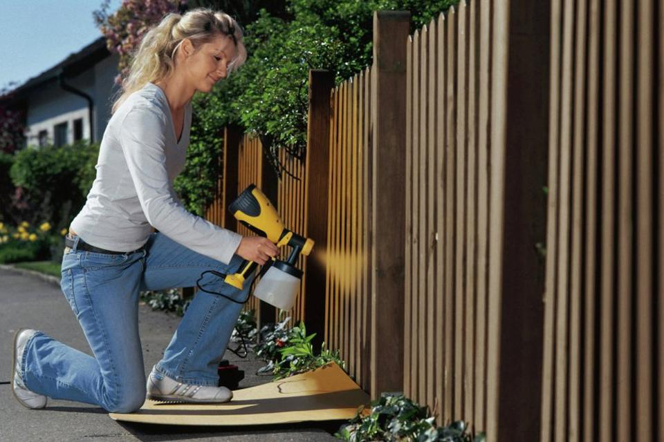 Woman spray painting a fence brown.