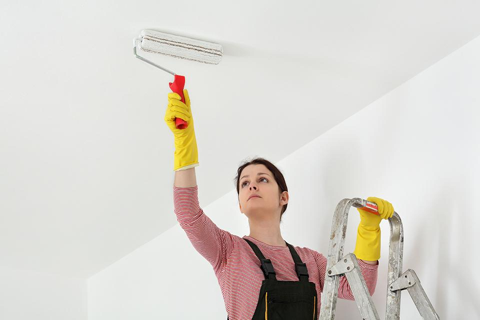 Woman on step ladder painting ceiling white with roller.