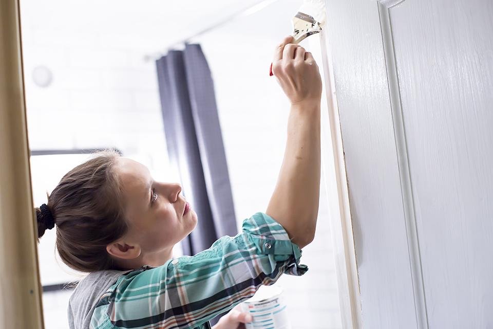 Woman using white paint on a doorframe.