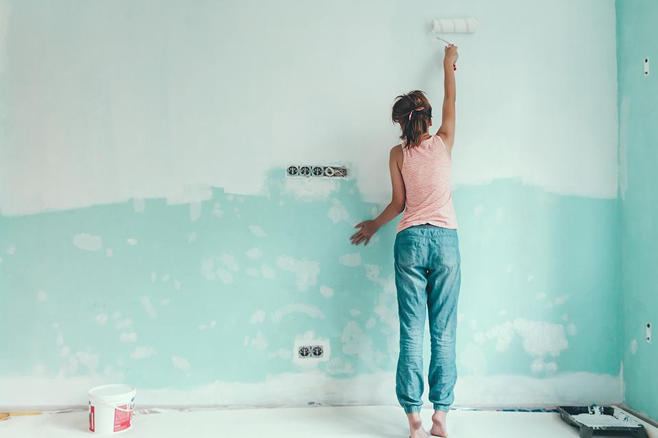 Woman using a roller to paint a wall duckegg.
