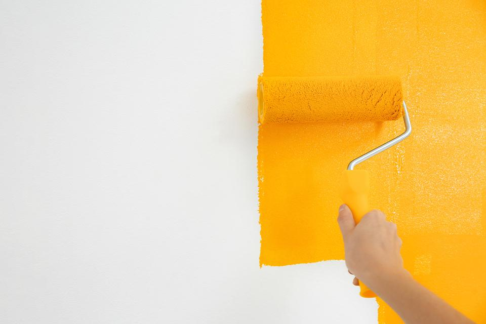 Person using a roller to paint a wall yellow.