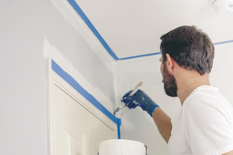 Man cutting in white paint around doorframe.