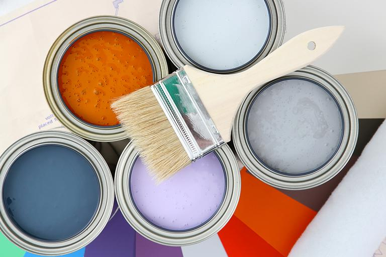 Pots of coloured paint and paint brush.