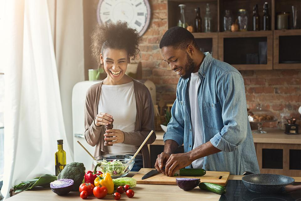 Man and woman laughing and preparing food in kitchen.