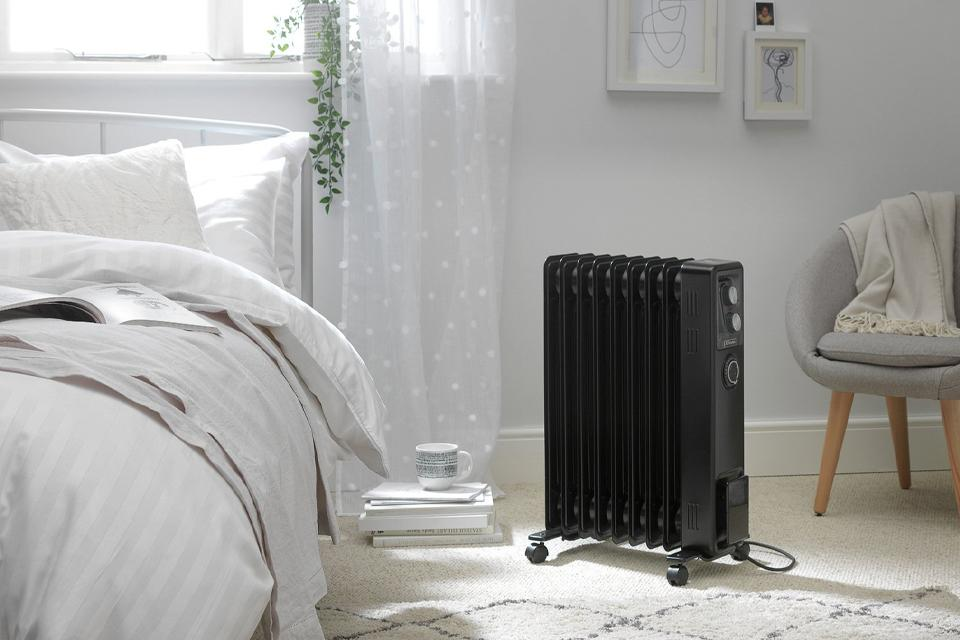 Portable radiator next to bed in bedroom.
