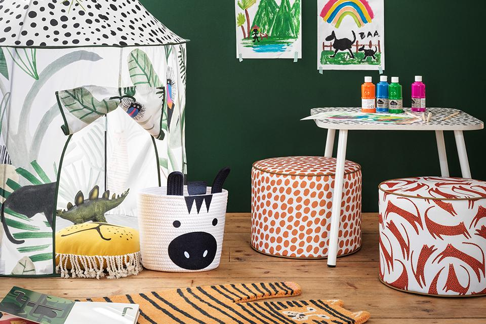Image of a green kids' room with a craft desk, pouffes and tent.