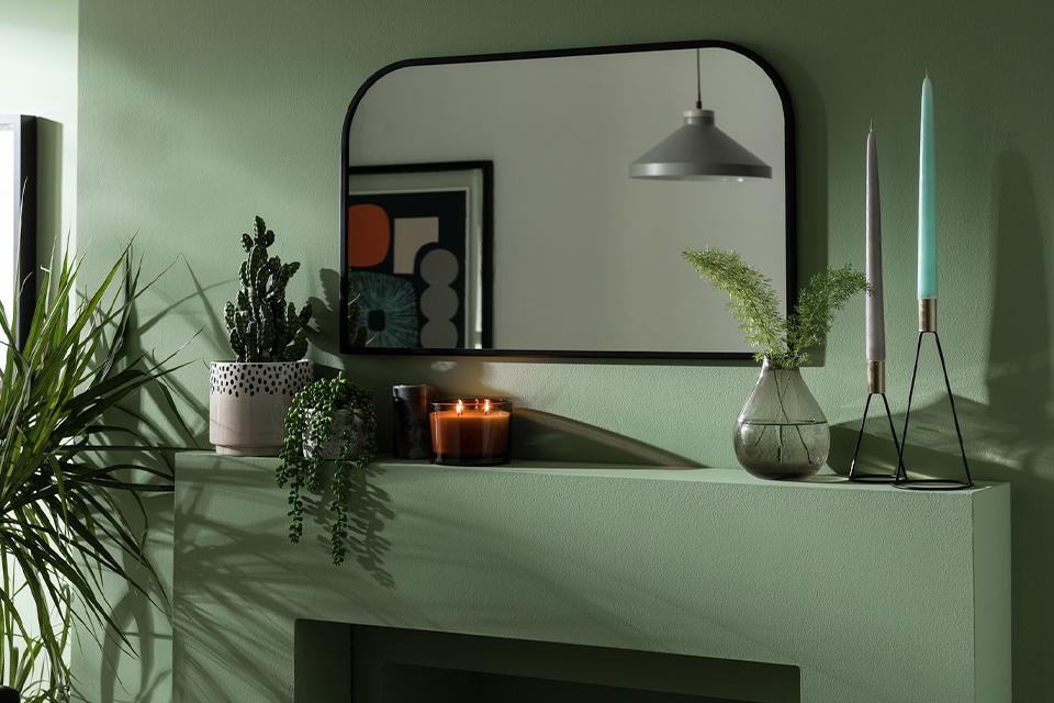 Image of a green mantlepiece with a mirror, candles and plants.