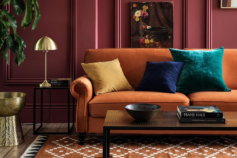 Image of an orang velvet sofa in a deep fuschia living room.
