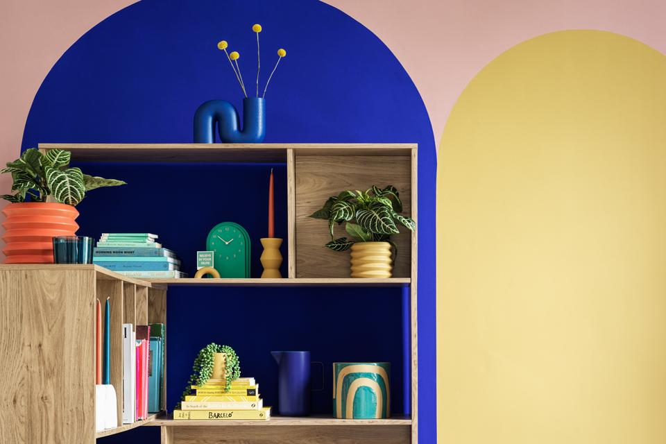 Image of a tall bookshelf with plants, vases and candles on it.