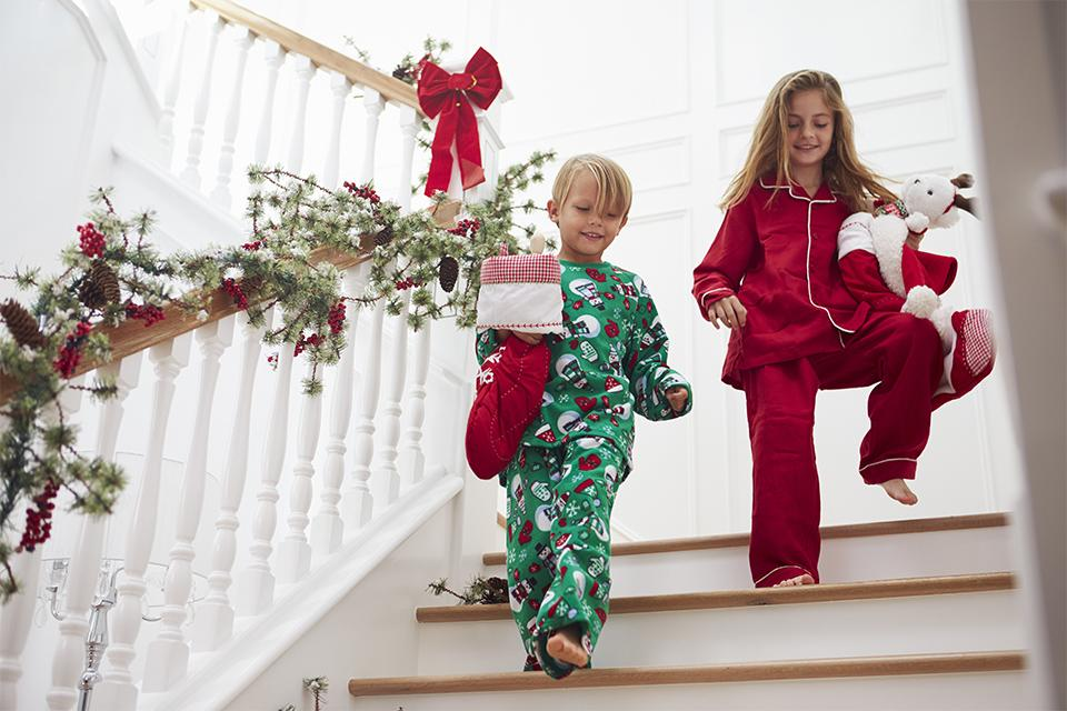 Kids running down stairs with stockings.