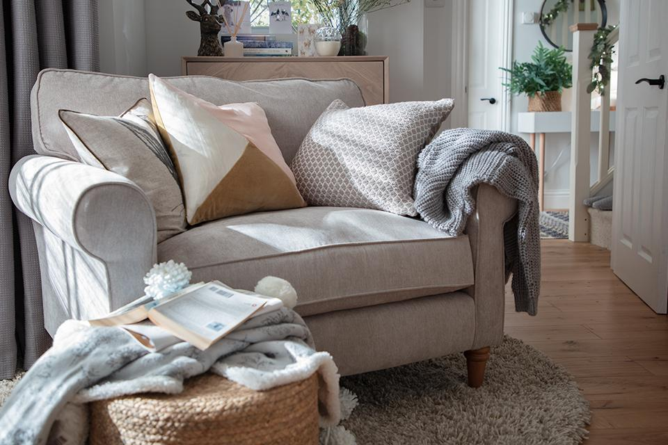 An image of an inviting cream coloured cuddle chair piled high with cosy cushions and throws.
