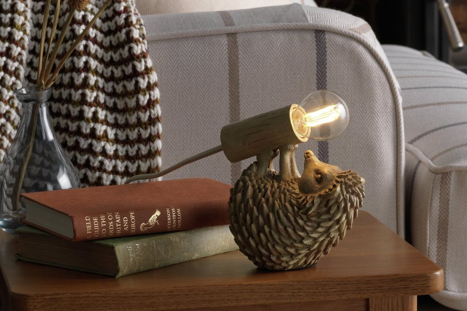 An image of a side table next to the arm of a fabric sofa. There's a unique lamp on the table, designed to look like a hedgehog is carrying the bulb.