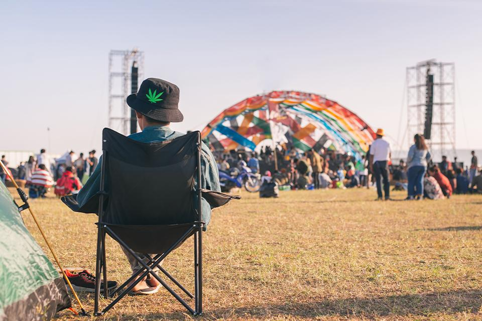 person sitting on a camp chair at a festival.