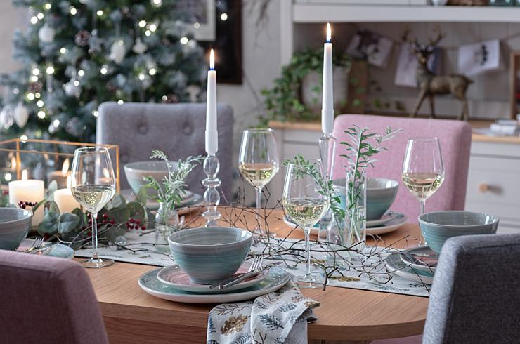 Wine glasses and candles on dining table.