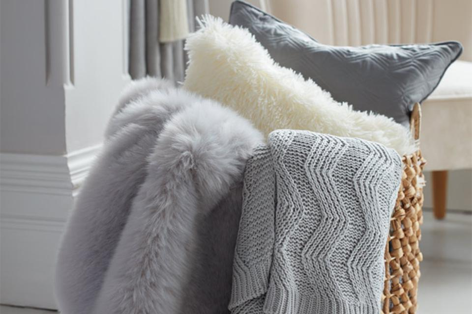 A selection of cream and grey throws and cushions.